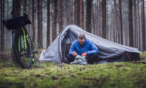 Image showing a man sitting in front of his tent in the forest.