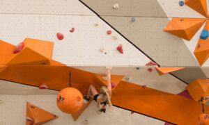 Image shows a woman bouldering