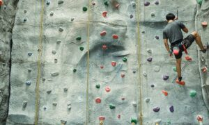 Man with safety harness climbing an indoor rock wall
