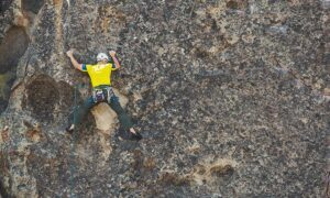 Image shows a man in a harness climbing a rock wall. Title: Outdoor climbing